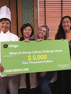The winner of the cook-off held at the Culinary Institute of America (CIA) in New York smiles in a commemorative photo shoot after receiving prize money of<br>5,000 USD from CJ CheilJedang''s Food Marketing Division general manager Eun-kyung Son
